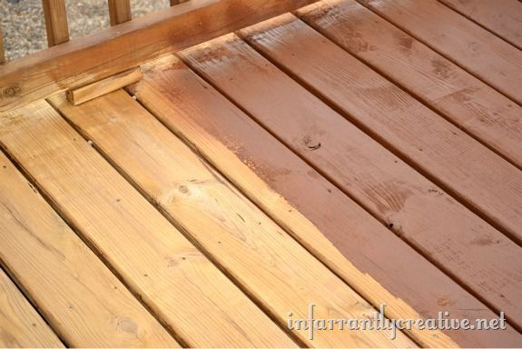 spraying a deck with stain